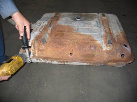 1. After the gas tank is de-fumed (cleaned) we drill holes in strategic locations to prepare for sandblasting.